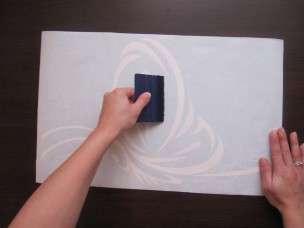 Hladítkem pečlivě uhlaďte přenosový papír tak, aby k němu samolepka dobře přilnula a naopak šla odlepit od podkladového (voskového) papíru.